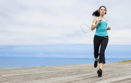 Beautiful young woman jogging on a boardwalk and listen music Фото со стока