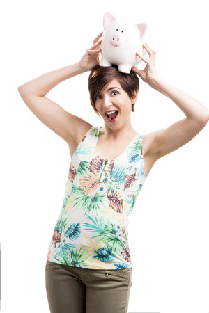 Beautiful happy woman holding a piggybank over her head, isolated over a white background