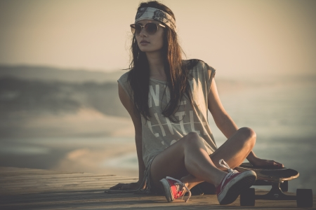 Mooie jonge vrouw zit op een skateboard