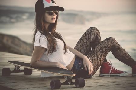 スケート ボードでポーズ美しいとファッションの若い女性 写真素材