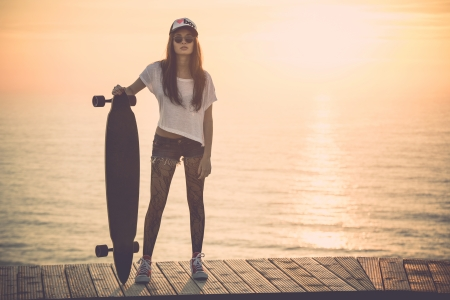 Beautiful and fashion young woman posing at teh sunset with a skateboard - File a little bit noisy