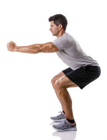 Athletic man running doing squats, isolated over a white background