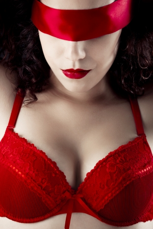 Sexy woman with a red lingerie and blindfolded