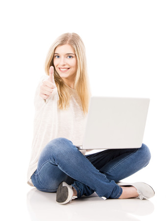 Beautiful and happy woman working on a laptop with thumbs up, isolated over white background
