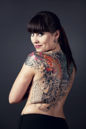 Portrait of a beautiful young woman with a tattoo on the backs