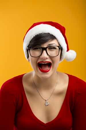 Beautiful nerd girl wearing a santa hat and holding a gift, against yellow background