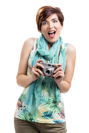 Astonished woman with a vintage camera, isolated over white background Imagens