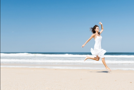 Beautiful girl in the beach enjoying the summer and jumping