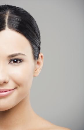 Beauty portrait de jeune femme asiatique souriante, sur un fond gris. Banque d'images