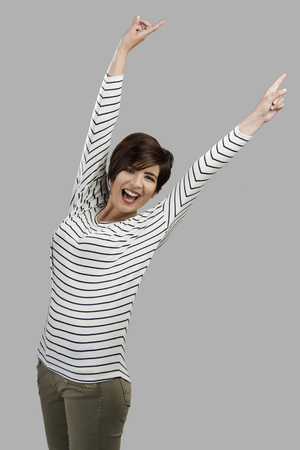 Portrait of a beautiful woman with arms on teh air, over a gray background