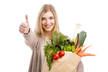 Beautiful blonde woman carrying a bag full of vegetables with thumbs up, isolated over white background Фото со стока