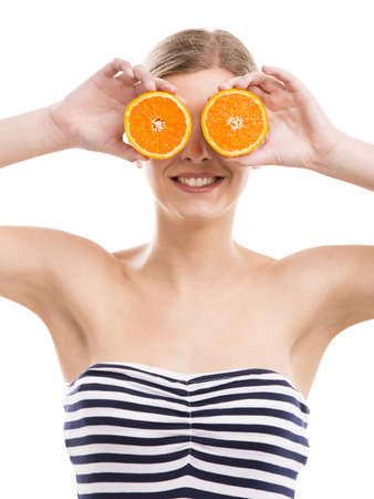 Beautiful woman holding orange slices in front of her eyes