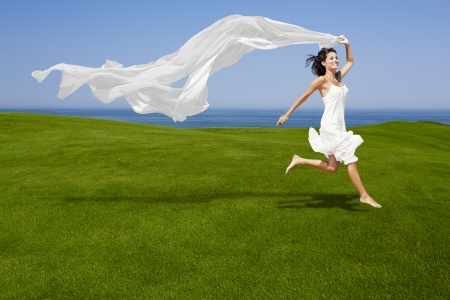 Beautiful woman running and jumping on a green meadow with a white tisue Фото со стока