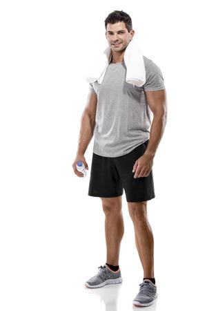 Portret van een atletische man na het doen van oefeningen en met een fles water, geïsoleerd op een witte achtergrond