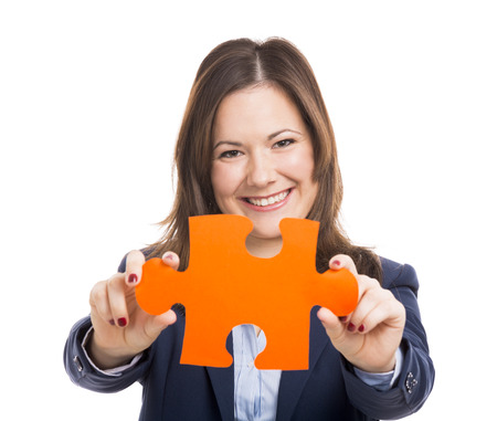 Business woman holding a puzzle piece, isolated over white