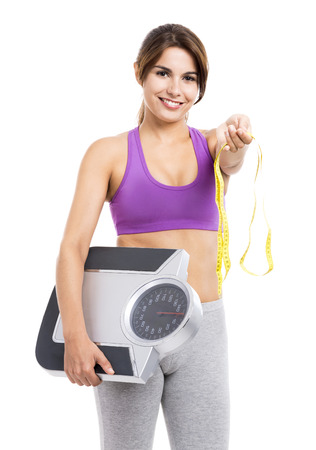 Beautiful athletic woman smilling and holding a scale and a measure tape, isolated on white
