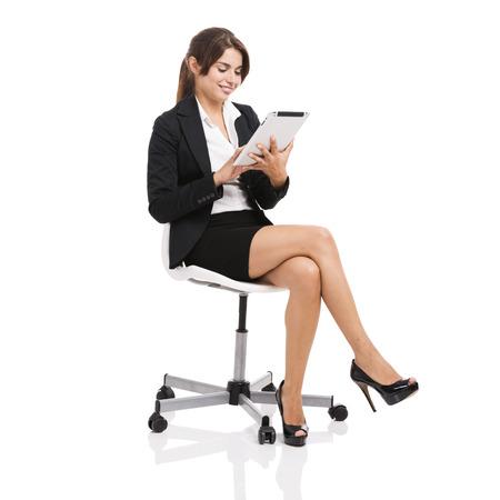 Gelukkig zakelijke vrouw zittend op een stoel te werken met een tablet, geïsoleerd over witte achtergrond