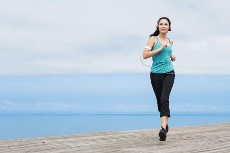 ボードウォークと耳を傾ける音楽のジョギングの美しい若い女性