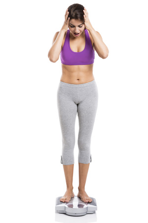 Beautiful and happy athletic woman over a scale with arms in the head, isolated on white background