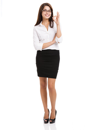 Beautiful and successful hispanic business woman doing a ok sign, over a white background