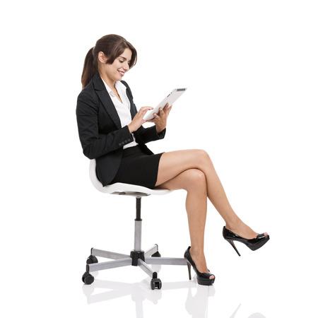 白い背景の上に隔離された、タブレットを使用して椅子に座って幸せなビジネスの女性