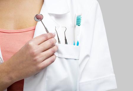 흰색 배경 위에 절연 도구로 여성 치과 의사,