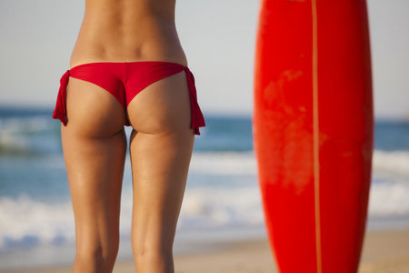 Back view of a woman in bikini with her surfboard