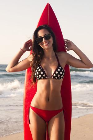 カゼルタヴェッキアと彼女のサーフボードとビーチでセクシーなサーファーの女の子