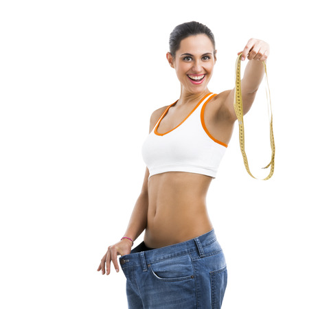 Woman with large jeans in dieting concept holding a measuring tape