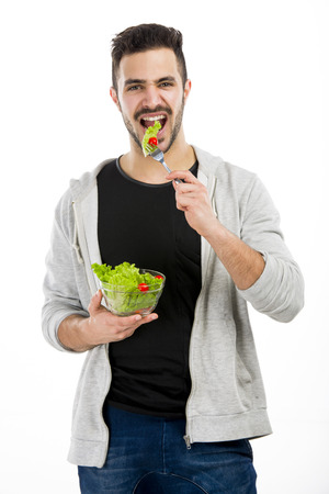 Happy young man eating a salad, isolated on white background Фото со стока