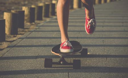 Jonge vrouw in de straat met een skateboard