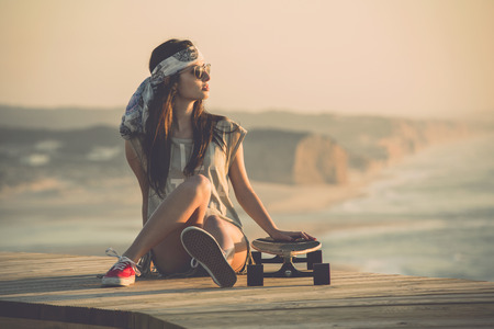 Beautiful young fashion skater girl looking at the sunset Фото со стока