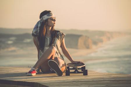 Mooie jonge mode-schaatser meisje te kijken naar de zonsondergang Stockfoto