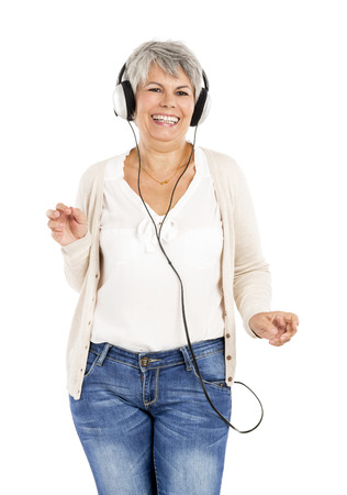 Elderly woman dancing while listen music with headphones, isolated over white background Фото со стока