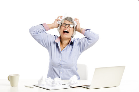 Stressed elderly woman working in the office with a laptop Banque d'images