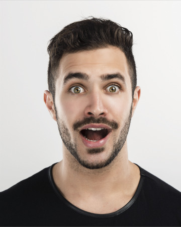 Studio portrait of a handsome young man astonished and happy expression