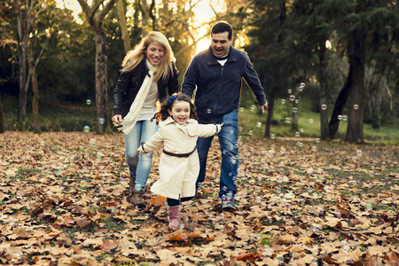 Outdoor portrait of a happy family enjoying the fall season Фото со стока