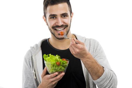 Gelukkig jonge man het eten van een salade, geïsoleerd op witte achtergrond Stockfoto