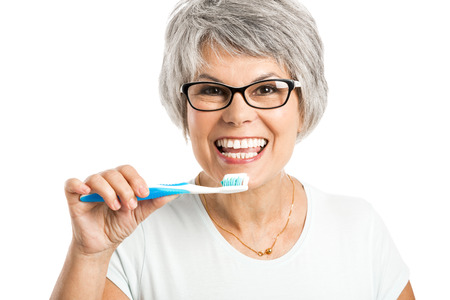 Portrait of a happy old woman brushing her teeth Banque d'images