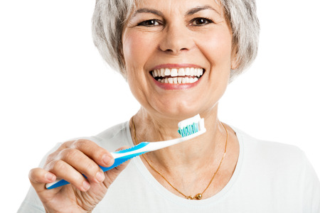 Portret van een gelukkige oude vrouw haar tanden poetsen Stockfoto