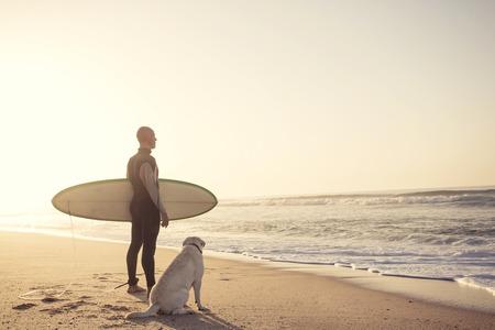 Surfist op het strand met zijn beste vriend Stockfoto
