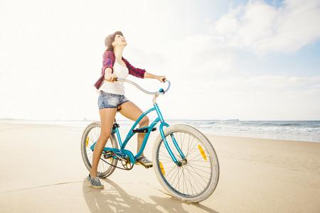 해변에서 그녀의 자전거를 타고 매력적인 젊은 여자 스톡 콘텐츠