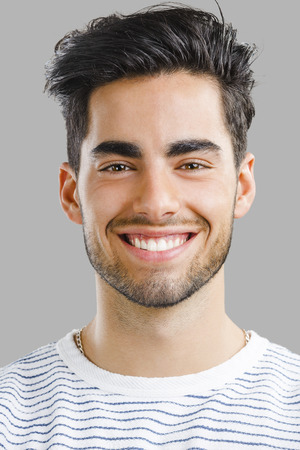 Close-up portrait of handsome young man,  isolated over a gray background Stock Photo - 40439585