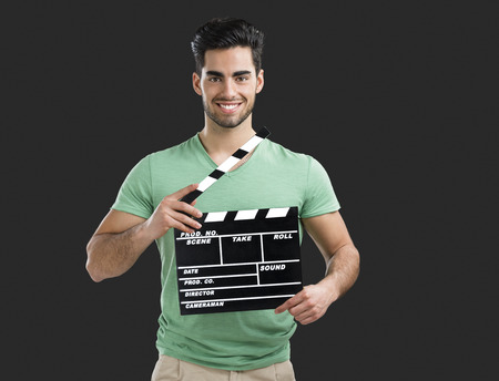 Portrait of handsome young man holding a clapboard, isolated on gray background 版權商用圖片