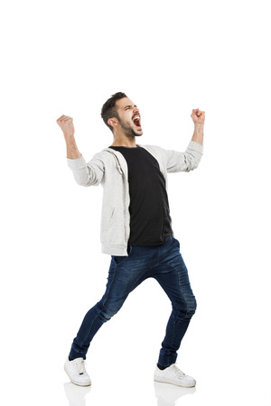 Successful young latin man with arms up