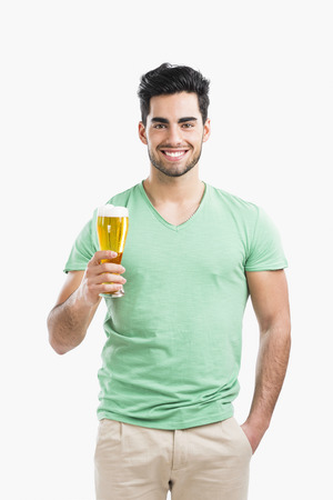 Portrait of handsome young man tasting a draft beer, isolated on gray background Фото со стока
