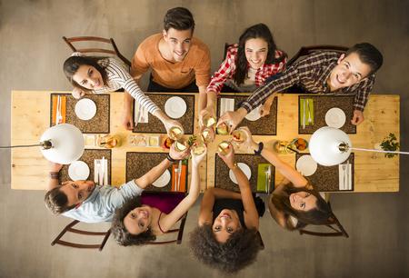 Groep mensen roosteren en op zoek gelukkig in een restaurant