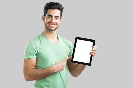 Handsome young man showing something on a tablet, isolated over gray background Фото со стока