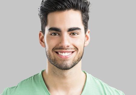 Portret van de knappe jonge man die lacht, geïsoleerd op een grijze achtergrond