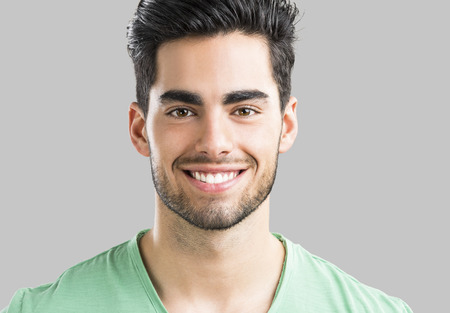 Portrait of handsome young man smiling, isolated on gray background Foto de archivo